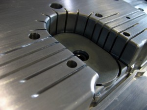Detail of the core of a plastic injection mould made of aluminum presenting some deep channels (to obtain high ribs) and inserts.